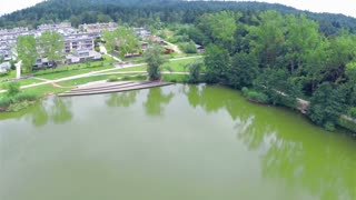 Aerial of nature conservation around apartments. Small lake near suburban apartments, with park and dock. Flying over.