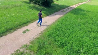 Aerial of Young Man Running on Sunny Day. Flying behind a person while running on track on a sunny day. Shoot from sky.