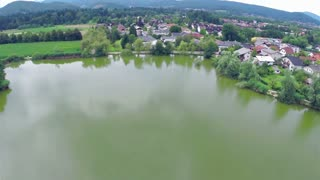 Aerial panning around lake. Small lake near suburban apartments, with park and dock. Flying over.