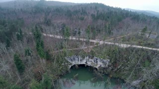 Aerial passing over a natural stone bridge with forest. Flying over a stone bridge with river running under.