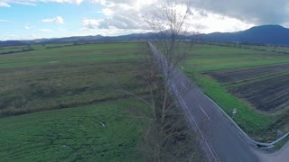Aerial shot of straight road through countryside. Wide shot of tree and road in background going to small village and dark clouds showing bad weather.