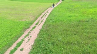 Aerial Wide shot of Tracking Runner on Track. Following person running on a trail between big lawns. Flying from above.