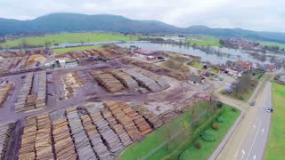 AERIAL: Wood industry. Flying over wood sawing industrial place, with a lot of stock of firewood.