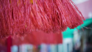 Beach umbrella strings in wind. Colorful red beach umbrella for sun shade in old town of Burano.