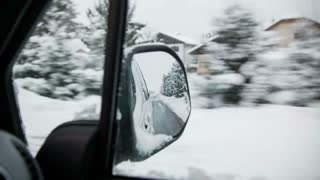 Beautiful snowy countryside from car seat. Driving through idyllic snow countryside with houses, reflection of road in car mirror.