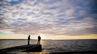 Beautiful sunset and fisherman at sea.Two fisherman under hoodie with fishing rod catching fishes in sea at dawn wide lens with colorful clouds.