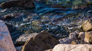 Bicycle in sea water. Lost bicycle in sea water between the rocks. Pollution of ocean.