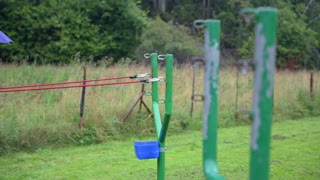 Big iron slingshot fires projectile. Close up on green iron slingshot placed on lawn, rubber stretched and fires.