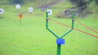 Big slingshot shot and hit the target. Focus pulling from stretching huge slingshot and hitting the target on field.