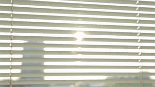 Blinding sun in the morning through roller blind