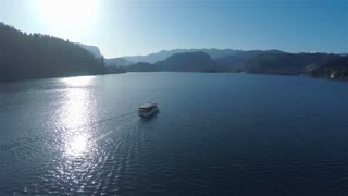 Boat on lake water on sunny day aerial 4K. Flying behind a tourist boat on lake Bled with sun shining on water surface.