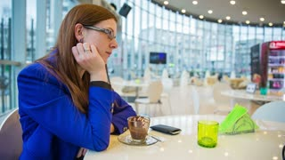 Bored woman waiting for date at cafe. Beautiful elegant female person at cafe waiting for someone and eating hot chocolate dessert of boredom.