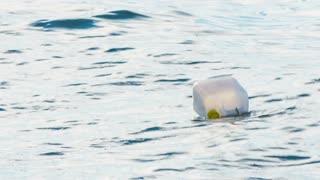 Bottle in sea. Abandoned bottle on sea surface wavy water.
