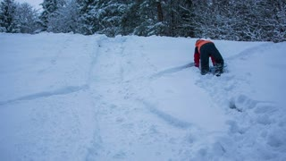 Boy climbing on top of snow hill. Young person hiking uphill in snow to drive down with plastic sleigh board.