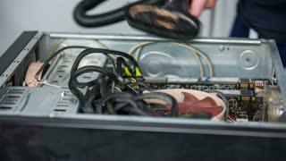 Brushing inside of computer. Technician cleaning inside of computer at workshop with vacuum-cleaner.
