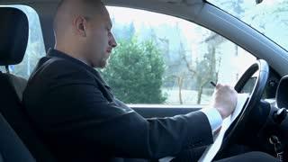 Businessman Writing Cancellation in Car