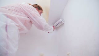 Carefully painting walls with paint roller. Paint job at home by woman in protective suit alone in slow motion.