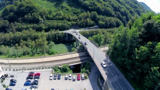 Cars driving over bridge with park place under aerial footage. Top view of main road going over river and railway. Green hills around.