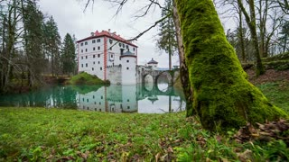 Castle Sneznik in nature jib shot. Wide shot of Slovenian castle surrounded with water, trees and green nature.