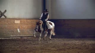 Cawgirl On Horse Galloping in Riding Hall
