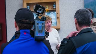 CERKNICA, SLOVENIA - OCTOBER 2014: TV news media doing interview with flood victim. Woman in front of camera explaining to reporters of the flood disaster around their house.
