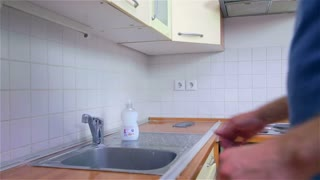 Cleaning kitchen tiles with sponge. Young attractive man in new home, checking and cleaning kitchen before using with own dishes.