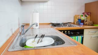 Cleaning kitchenware under water in kitchen. Close up of male person cleaning plates and kitchenware with water from pipe and sponge.