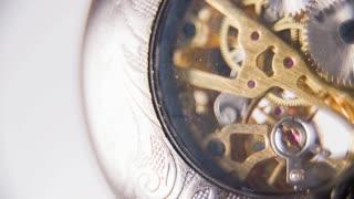 Clock Mechanism in Vintage Pocket Watch in Slow Motion. Analogue pocket watch slow motion ticking mechanism on white background macro.