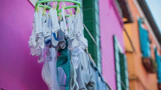 Clothes hanging from window drying. Drying clothes on a sunny day, handing from colorful building in Burano, Venetian Lagoon town on sea.