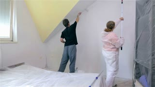 Couple painting new room. Man and woman working together painting room with fresh white color.