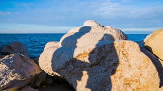 Couple shadows kissing at sea. Seascape with big rocks in front with shadow of two person kissing.