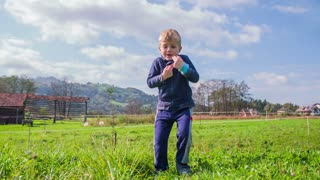 Cute boy jumping on grass. Kid in slow motion jumping and want to be a ninja.