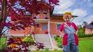 Cute Kid With Helmet Proud in front of House
