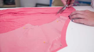 Cutting new dress with scissors high angle close up. Tailor cutting pieces from blank textile for new elegant dress with measured plastic foils.