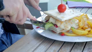 Cutting special sandwich with fries close up. Male in restaurant outside sitting behind the table and eating food.
