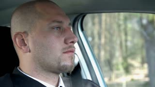 Depressed Look on Businessman While Driving Car