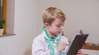 Doctor kid writing report to patient. Young boy playing medical staff in clinic with stethoscope around neck and writing report in slow motion.