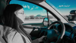 Driving car in black and white with blue tint. Inside car shot of woman driving on highway, colorless video only blue color of sky.