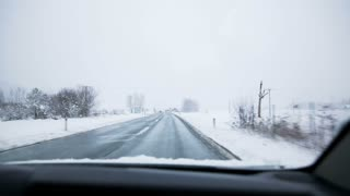 Driving in snow. Traveling on plowed road on a snow day with whole countryside in white.