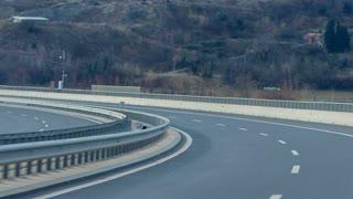 Driving on empty highway bridge. Personal driver view while driving on empty wide highway while no one around. Bumpy ride.