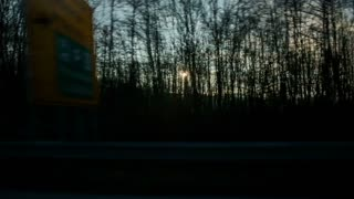 Driving on highway with sunset through trees. Speeding on highway with side view through windows of sunset behind the trees.