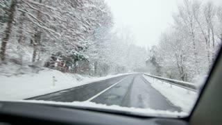 Driving on snowy road. Car passenger perspective view while driving through woods road while snowing.