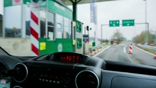 Driving through toll station. Inside car shot of driving through toll station with fence lifting up and LED sign showing green light.