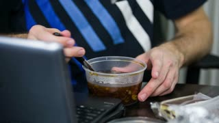 Eat soup while working on computer. Person ordering food in plastic boxes while working job on personal computer, close up.