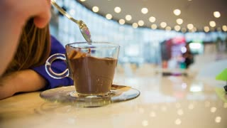 Eating hot chocolate dessert from cup close up. Female person enjoying hot chocolate pudding at cafe.
