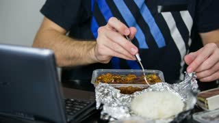 Eating rice with chicken in hot sauce. Close up of person behind the table with laptop and packed boxes with food eating.