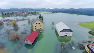 Farm with barnhouse in flooded water. Aerial shot over farmland with objects in water after flood in Slovenia.