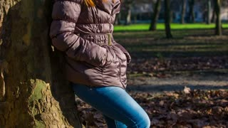 Female person hands in jacket pockets. Close up of woman belt while leaning on old tree and waiting in green park.