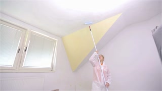 Female person paint ceiling with water based color. Preparing walls before adding fresh white paint. Adding mixture of water for color to better perform.