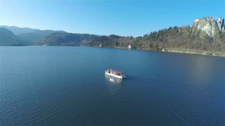 Fly around a boat on lake Bled with castle in 4K. Tourist boat traveling over lake Bled, circling around with view on old famous castle and mountains Alps in background.